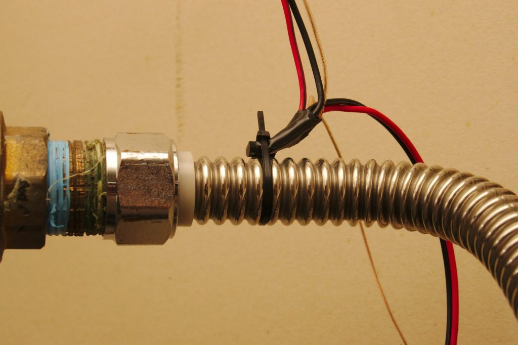 A sensor zip-tied to a pipe